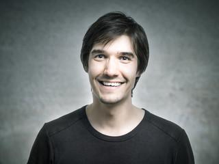 Junger Mann grinst fröhlich vor sich hin.