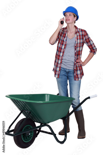 Woman with wheelbarrow and radio receiver