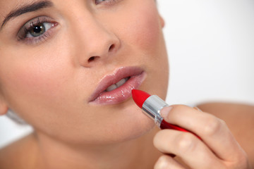 Woman applying red lipstick