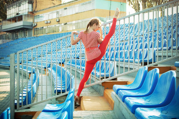 Sporty woman is working out on stadium