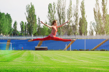 Sporty woman doing gymnastic exercise on stadium