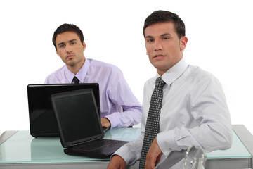 Two businessmen sat at the same desk