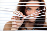 A cute brunette spying through the blinds.