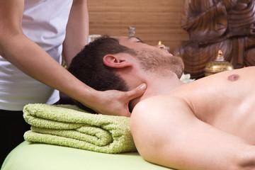 Mann wird am Nacken massiert - Thai-Massage