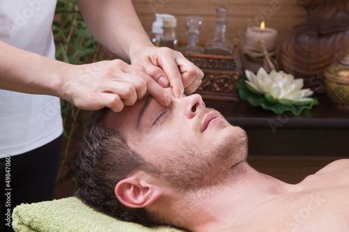 Attraktiver Mann bekommt eine Gesichtsmassage