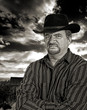 Rancher scowling with stormy sky in background