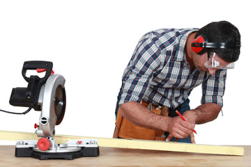 Carpenter marking wood before sawing