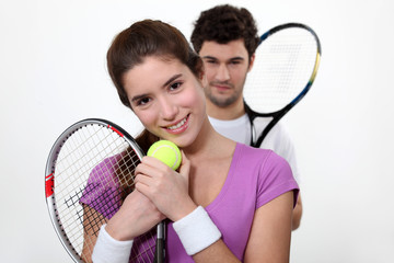 Young couple with tennis racquets