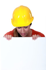 Female manual worker staring at blank poster