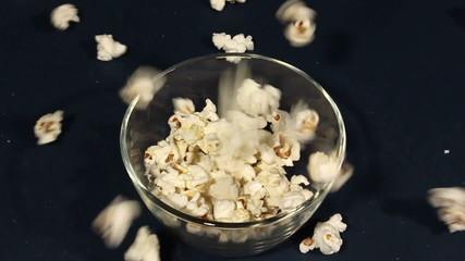 Popcorn falls in a glass cup. Close up scene