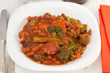 meat with sausages and vegetables on the white plate