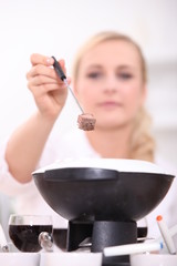 Woman eating a fondue bourguignonne