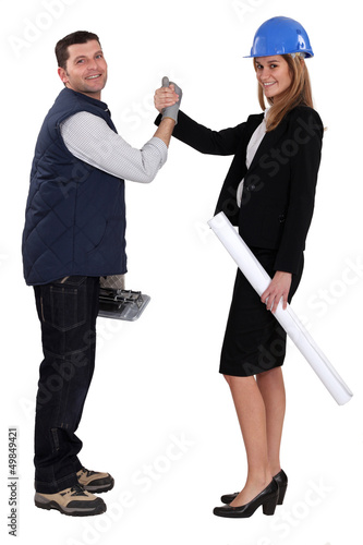 Architect and construction worker shake hands