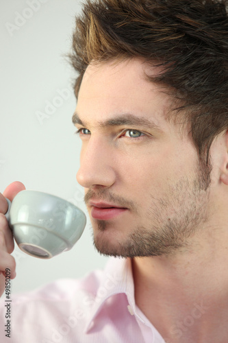 Young man drinking a cup of expresso