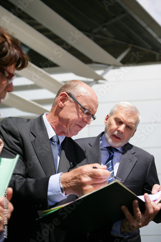 Businesspeople consulting a file outside