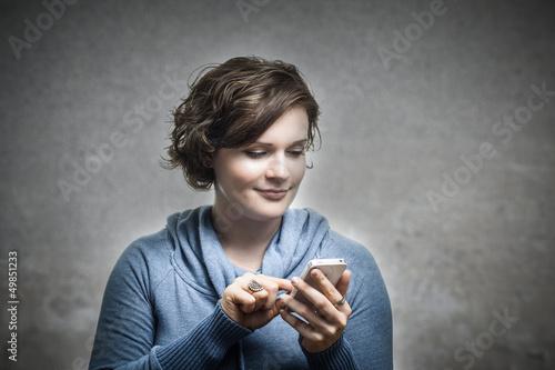 Junge Frau spielt mit ihrem Telefon rum.