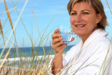 Woman with a bathrobe and a glass of water at the beach