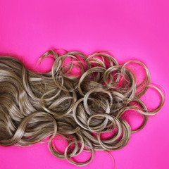 curly brown hair over pink background