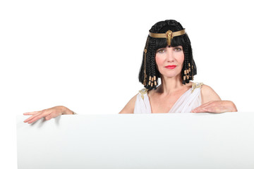 Woman in Cleopatra costume with blank board ready for text