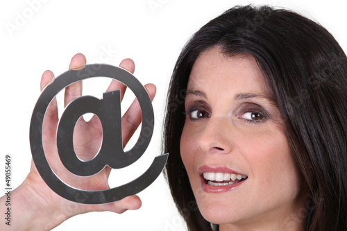 Woman holding an @ sign