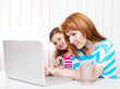Young woman with daughter using laptop computer