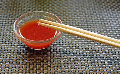 glass bowl with hot sauce with chopsticks Chinese restaurant