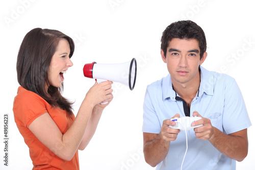 Girl screaming into megapgone whilst boyfridnd plays vide games