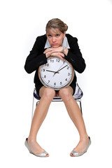 Upset woman sat with clock
