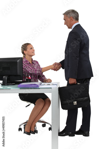 Businessman shaking hands with his new secretary