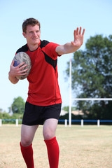 Rugby player holding the ball tight to his chest mid game