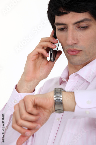 Businessman checking the time during call