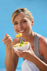 happy blond woman eating fruit salad