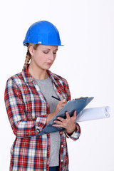 Female construction worker writing on clip-board