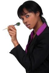 Businesswoman holding dart