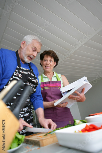Mature couple cooking with cookbook