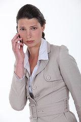 A sad businesswoman over the phone.