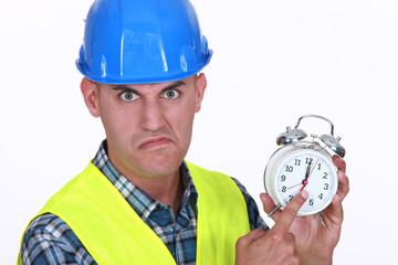 Angry foreman holding alarm clock