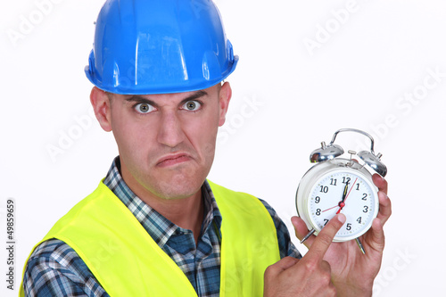 Angry foreman holding alarm clock