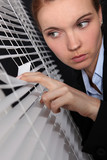 businesswoman looking through the blinds