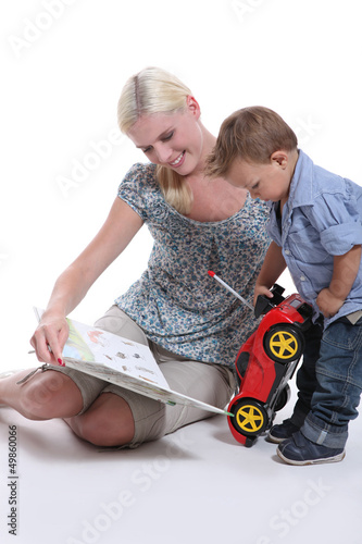 a mother showing a book to her little boy playing with a car