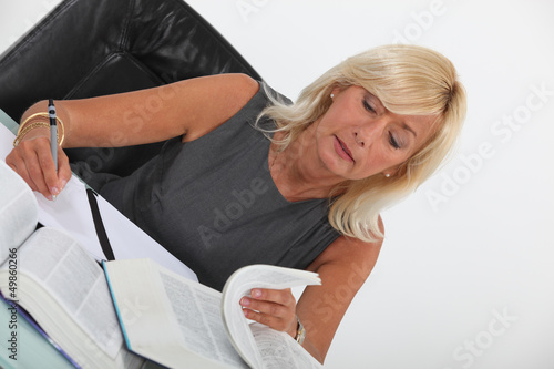 Woman looking through text books
