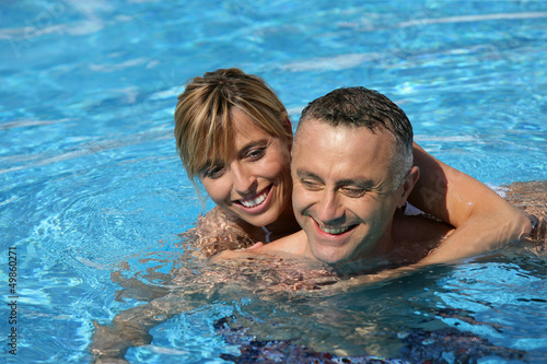Couple swimming in hotel pool