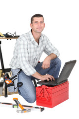 Handyman kneeling by laptop and tool kit