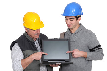 Father and son builder team pointing at laptop