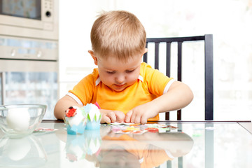 child boy decorate easter eggs indoors