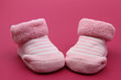 Pink baby socks on pink background