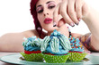 Junge Frau im Pin Up Style dekoriert verspielt Cupcakes