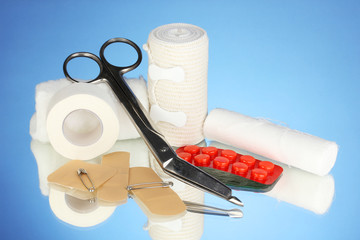 First aid kit for bandaging on blue background