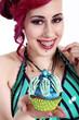 Junge Frau mit Zahnspange serviert lachend Cupcake