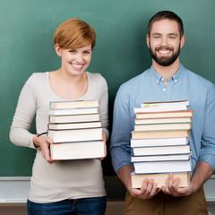 zwei studenten tragen schwere bücher